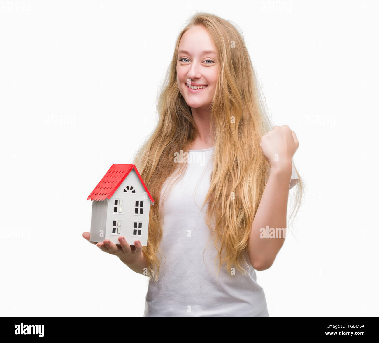 Blonde teenager woman holding family house screaming proud and celebrating victory and success very excited, cheering emotion - Stock Image
