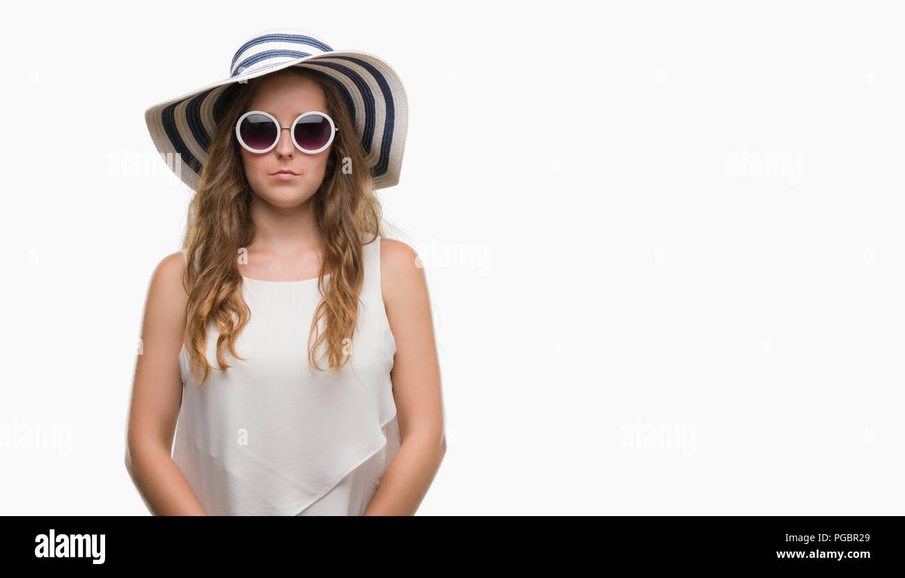 Young blonde woman wearing sunglasses and summer hat with a confident expression on smart face thinking serious - Stock Image