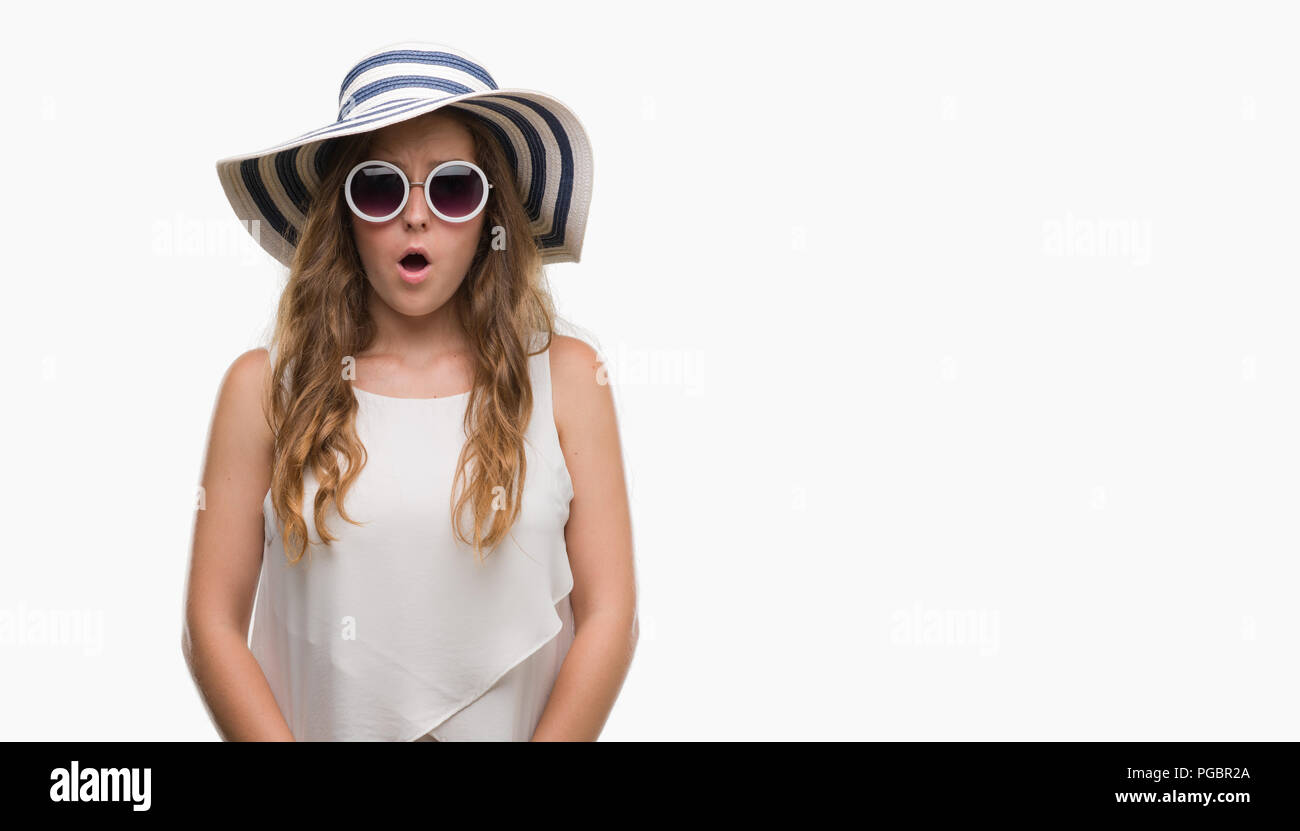 Young blonde woman wearing sunglasses and summer hat scared in shock with a surprise face, afraid and excited with fear expression - Stock Image
