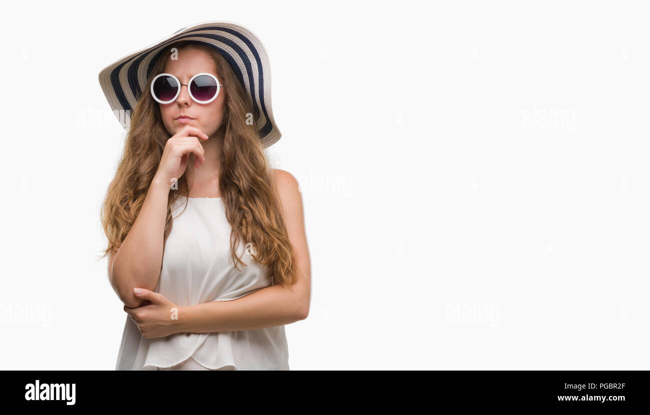 Young blonde woman wearing sunglasses and summer hat serious face thinking about question, very confused idea - Stock Image