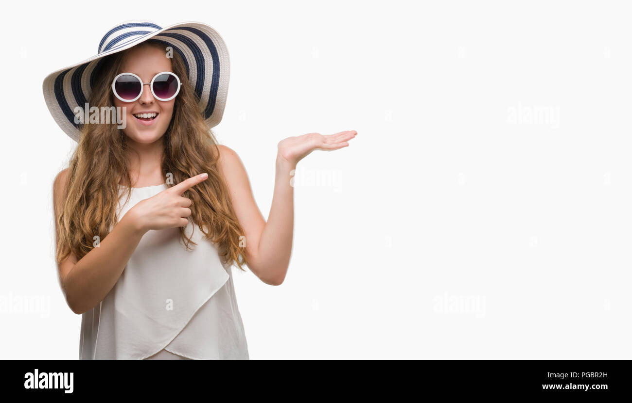 Young blonde woman wearing sunglasses and summer hat very happy pointing with hand and finger - Stock Image