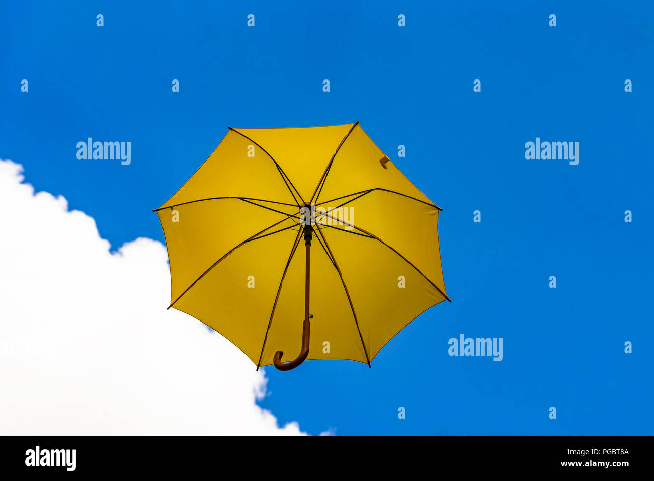 Flying yellow umbrella on a blue sky with white cloud - Stock Image