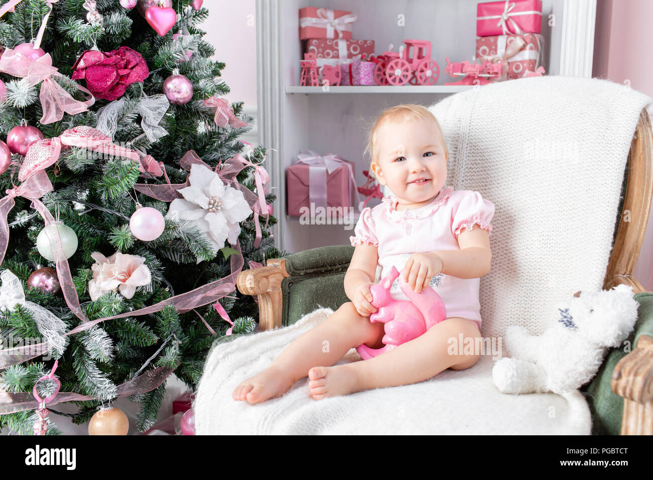 Cute little baby in vintage chair and christmas gifts. Little child ...