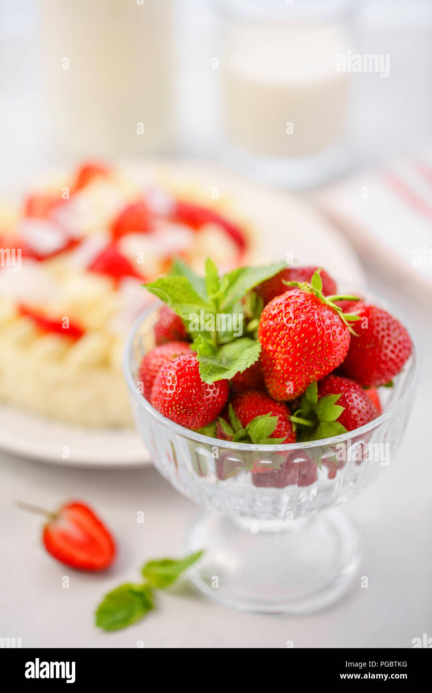 focus on strawberries . Delicate strawberry cheesecake with coconut. Delicious homemade cake with Fresh berries on light table. - Stock Image