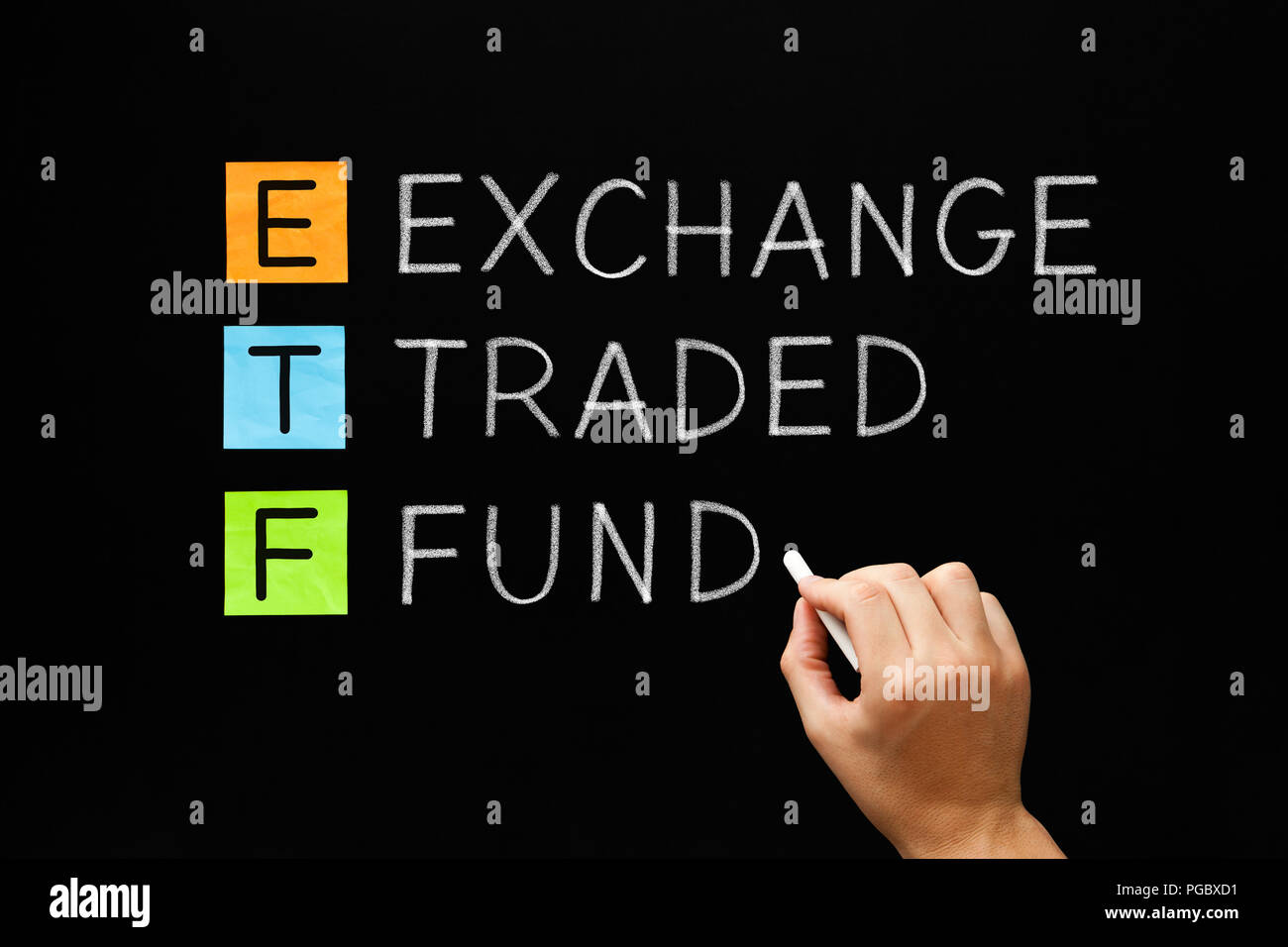 Hand writing ETF - Exchange Traded Fund with white chalk on blackboard. Stock Photo