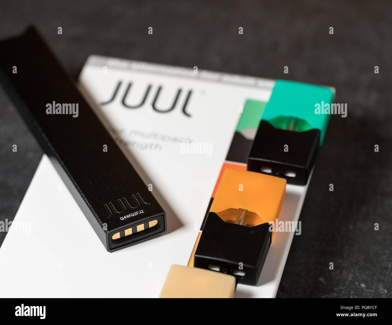 Box holding JUUL nicotine dispenser and pods Stock Photo