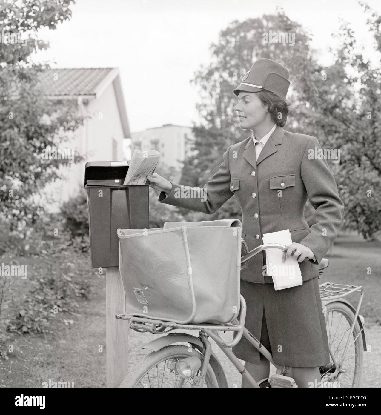 1960s postman. A woman in the swedish postal service uniform delivers mail and put the letters in a mailbox. Sweden 1960s.  Photo Kristoffersson DG114-7 - Stock Image