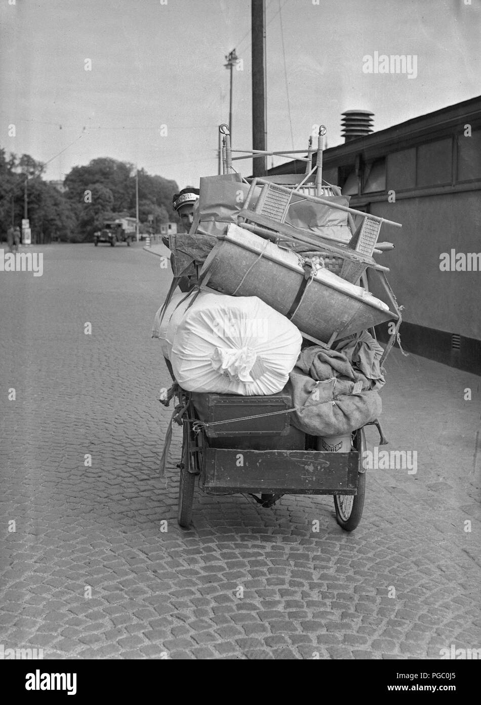 1940s transportation. A young man is working as a bicycle messanger and transporting goods in Stockholm city with his transport bicycle. June 1940.  Photo Kristoffersson 146-8 - Stock Image