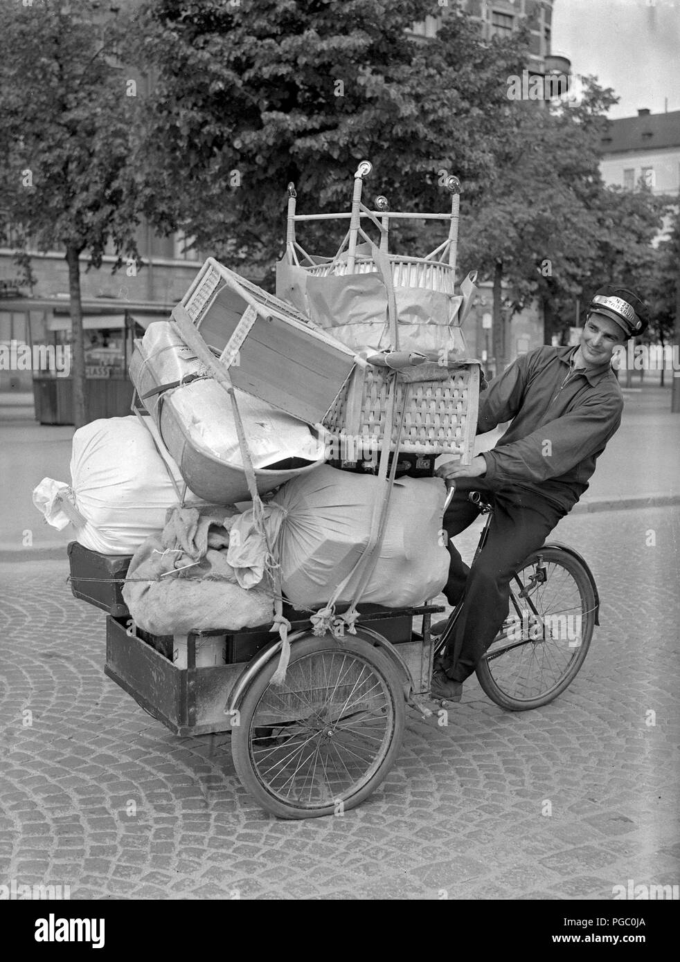 1940s transportation. A young man is working as a bicycle messanger and transporting goods in Stockholm city with his transport bicycle. June 1940.  Photo Kristoffersson 146-7 - Stock Image