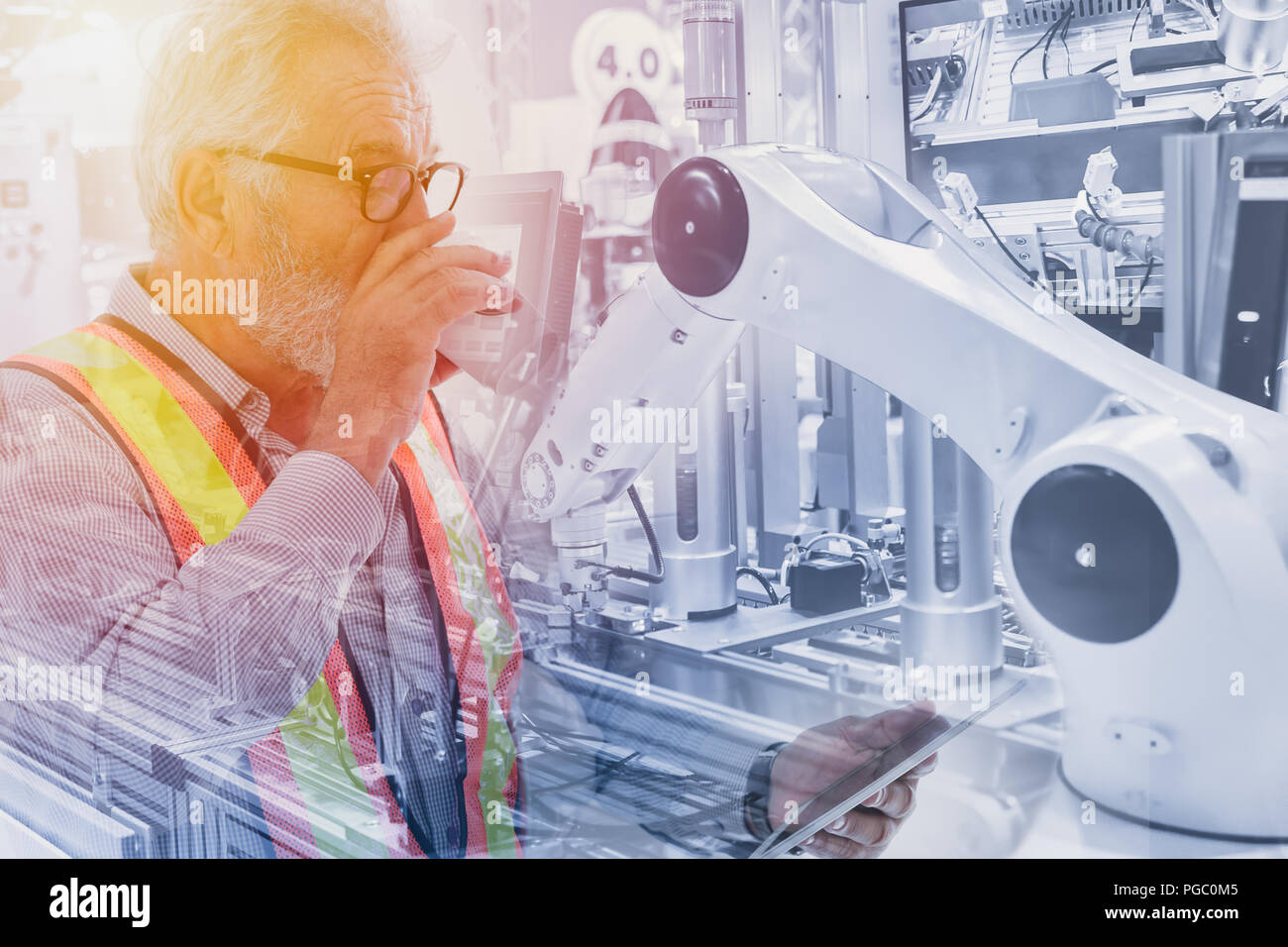 Engineer using tablet control robot arm in production line for robotic engineering concept - Stock Image
