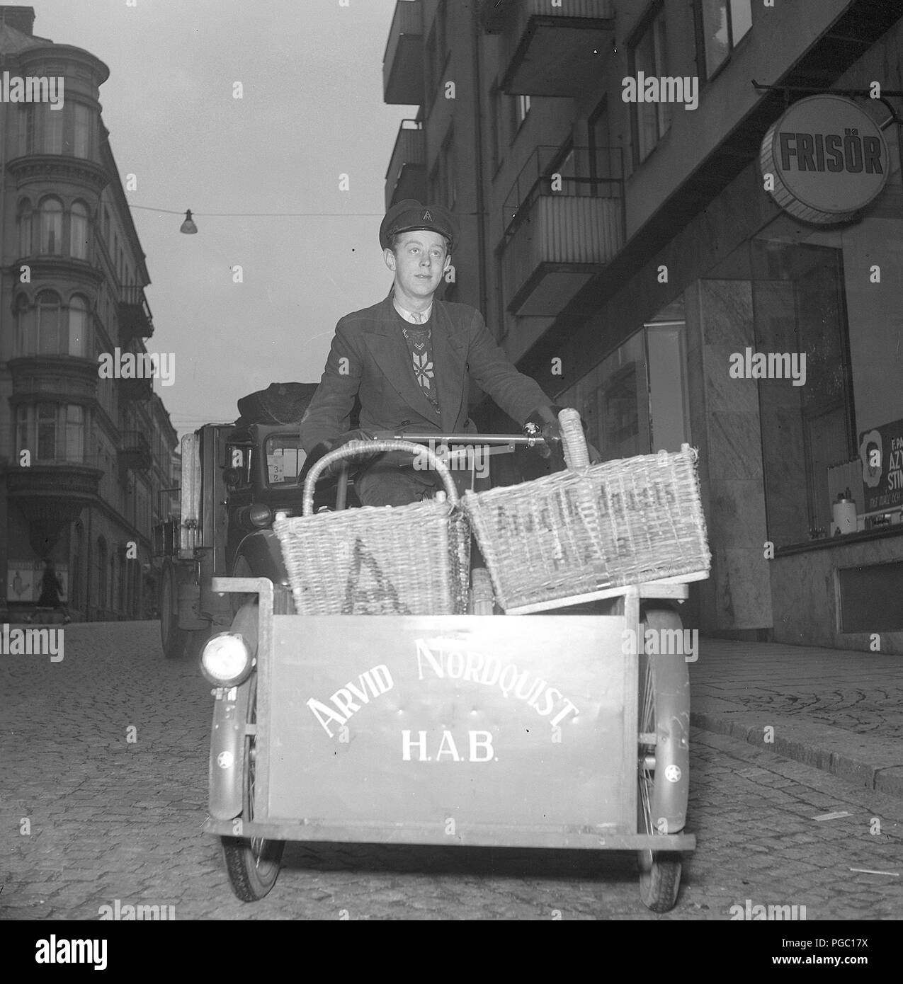 1940s bicycle transportation. A man working as a delivery man with groceries on his bicycle to be delivered to clients from the company Arvid Nordquist. Sweden 1940s.  Photo Kristoffersson A125-2 - Stock Image