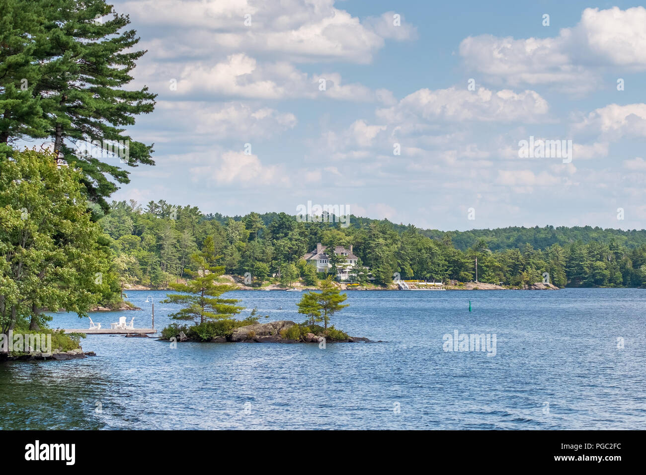 View of Lake Muskoka in Ontario Canada taken during the summer.  A cottage is seen in the background. - Stock Image