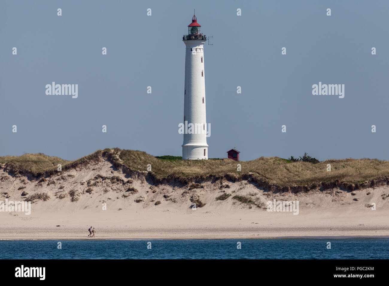 A couple walking on the beach as people stand on Lyngvig Lighthouse (Lyngvig Fyr) on the west coast of Jutland coast in Denmark. The lighthouse was built in 1906 and was the last built along this coast. Although no longer used for maritime navigation, it was built following a tragic accident at sea in 1903, where 24 sailors lost their lives. The light was lit for the first time on 3rd November 1906. - Stock Image