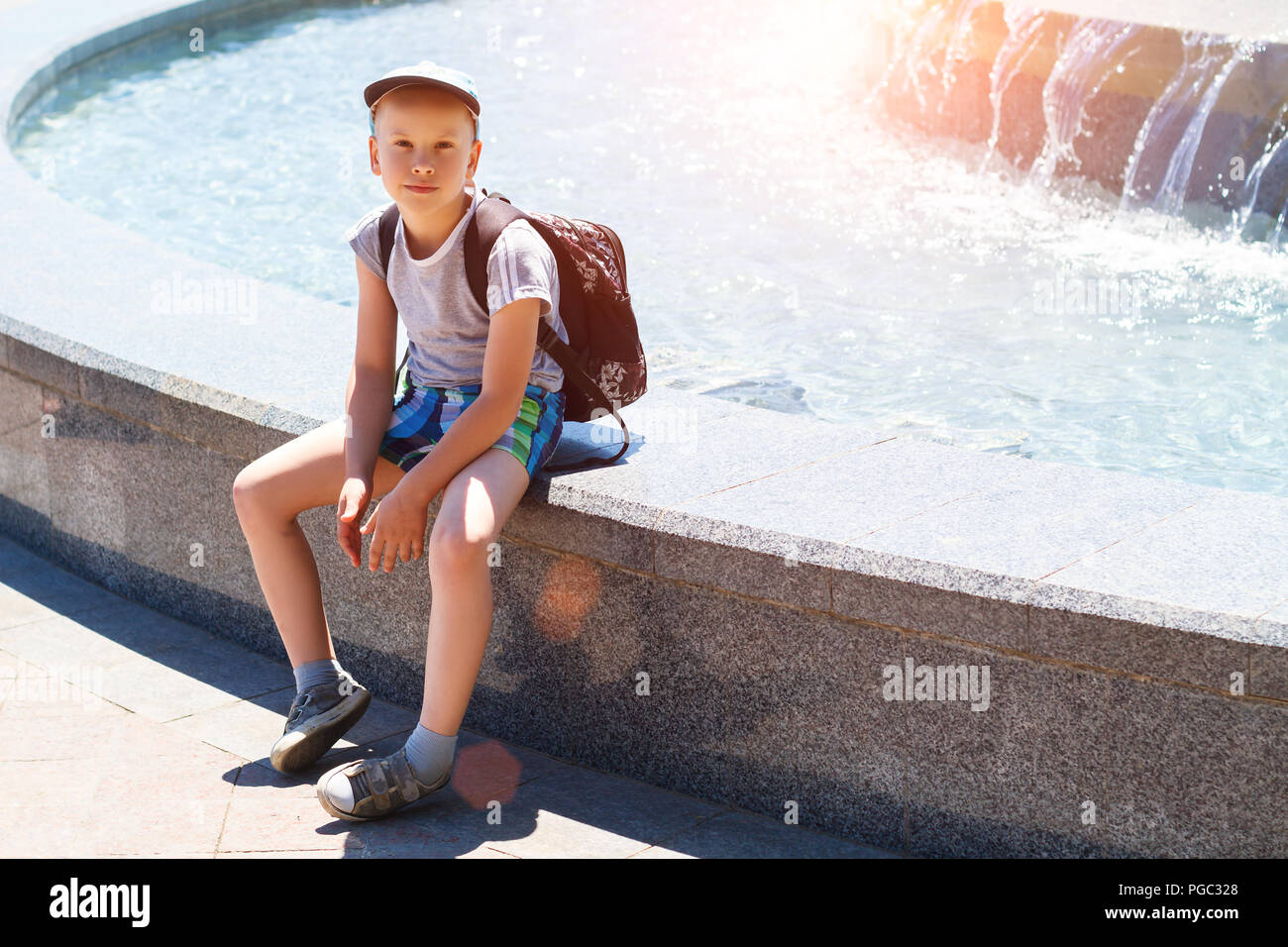 boy sitting by the fountain on a Sunny day Stock Photo