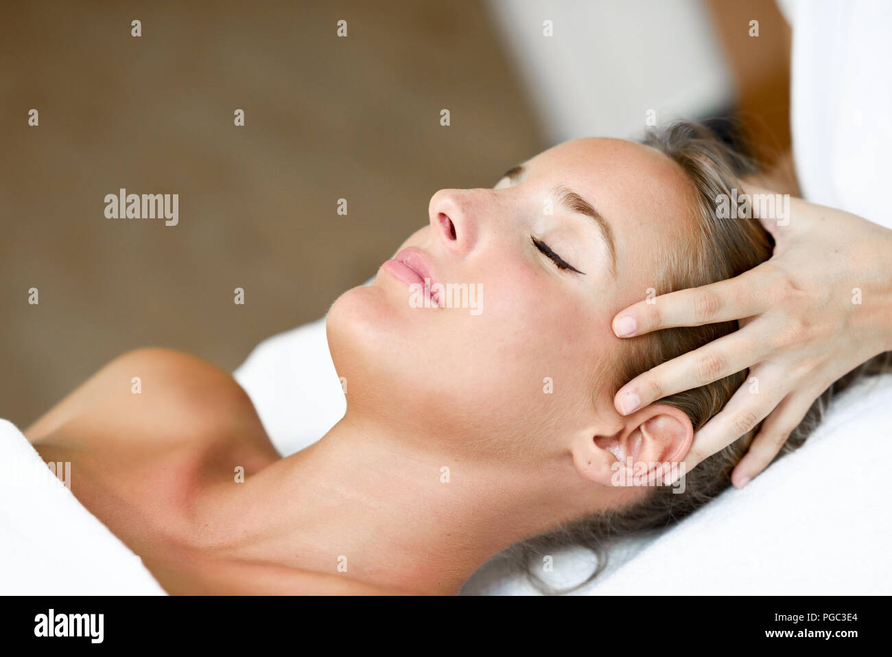 Young blond woman receiving a head massage in a spa center with eyes closed. Female patient is receiving treatment by professional therapist. - Stock Image