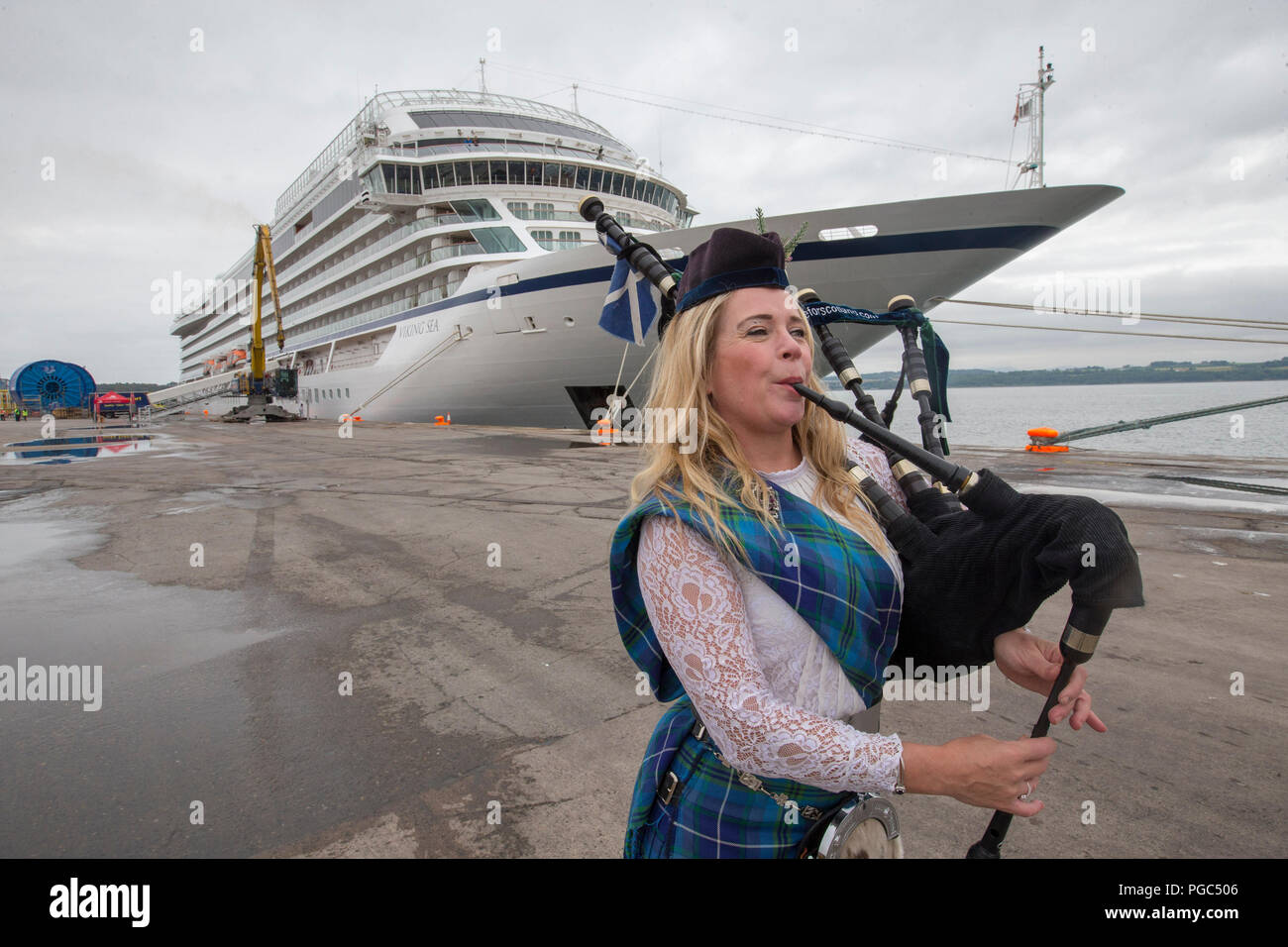 Female bag piper playing welcome for Cruise Liner - Stock Image