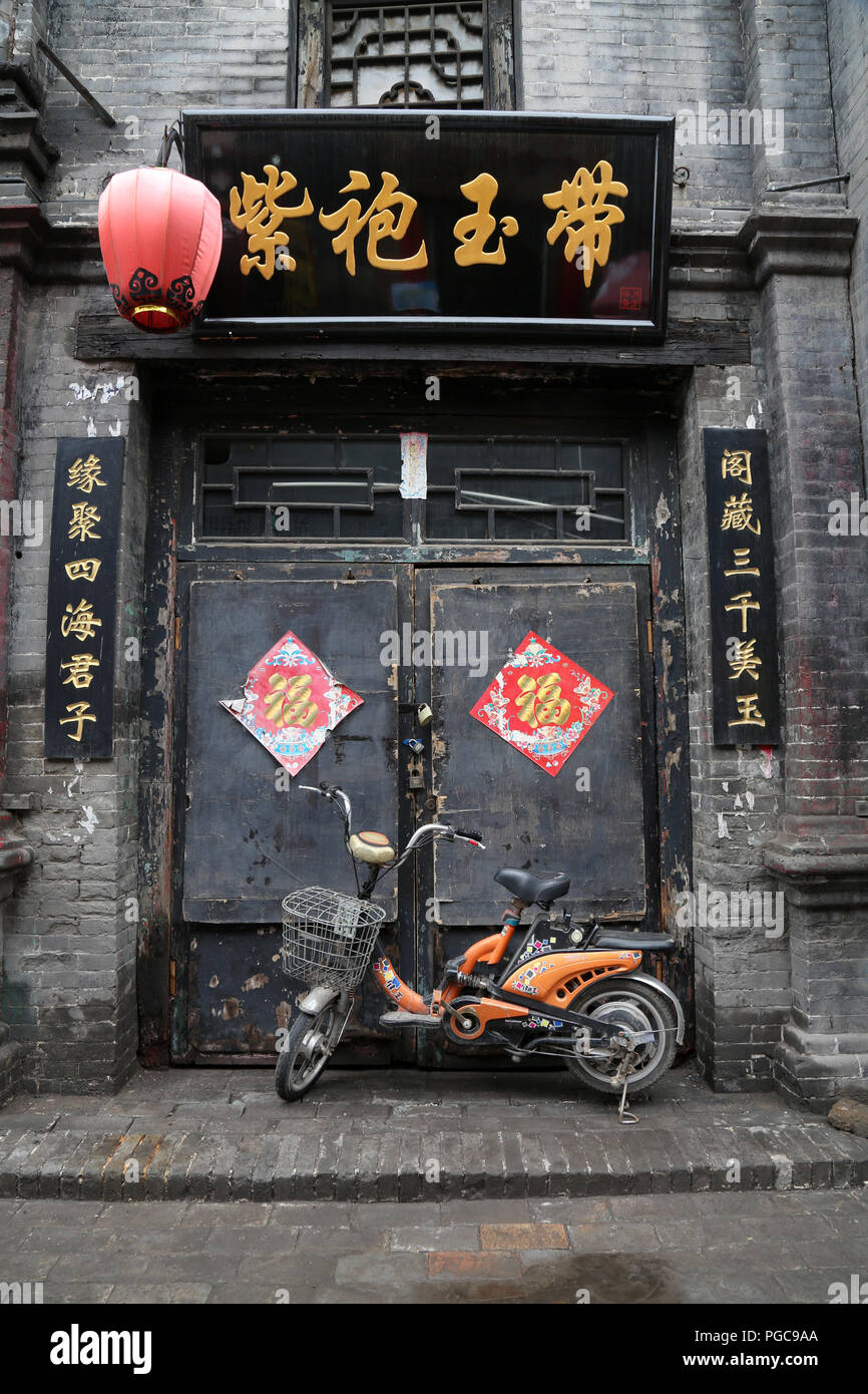 Door of a traditional house in Pingyao, China, with motorbike and Chinese writings Stock Photo