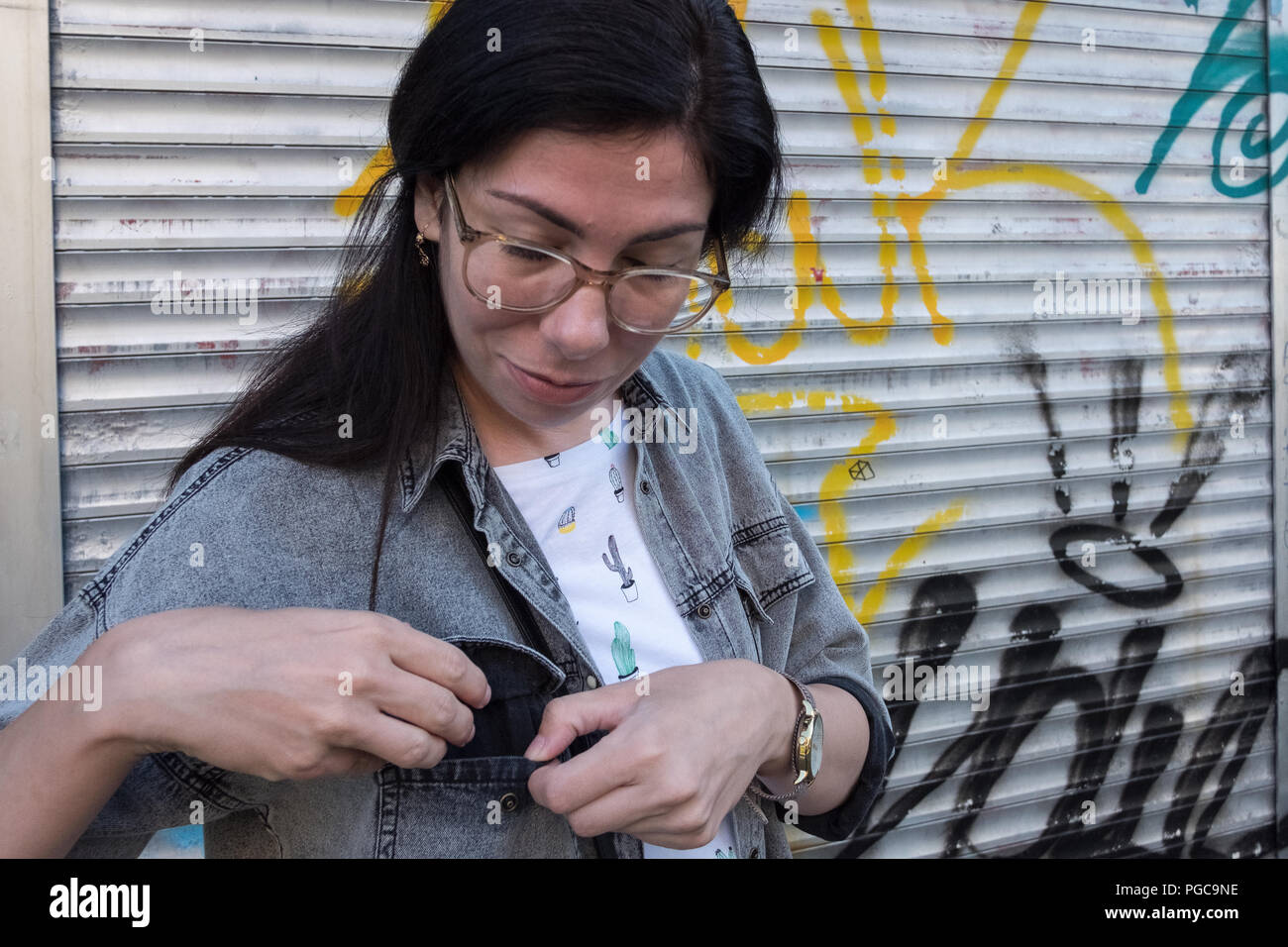 Young adult woman wearing glasses opening a shirt poket on the street, - Stock Image