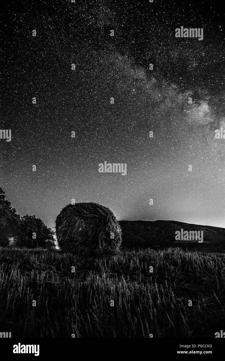 Beautiful view of starred night sky with milky way over a cultivated field with hay bale - Stock Image