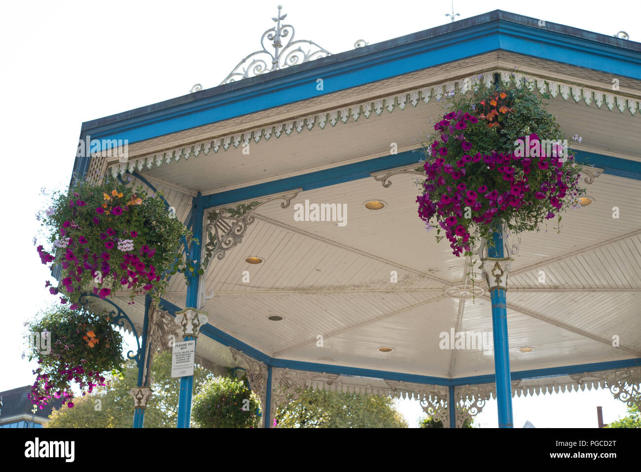 The floral displays around the bandstand roof in the Carfax of Horsham town center. Summer flowers in hanging baskets. - Stock Image