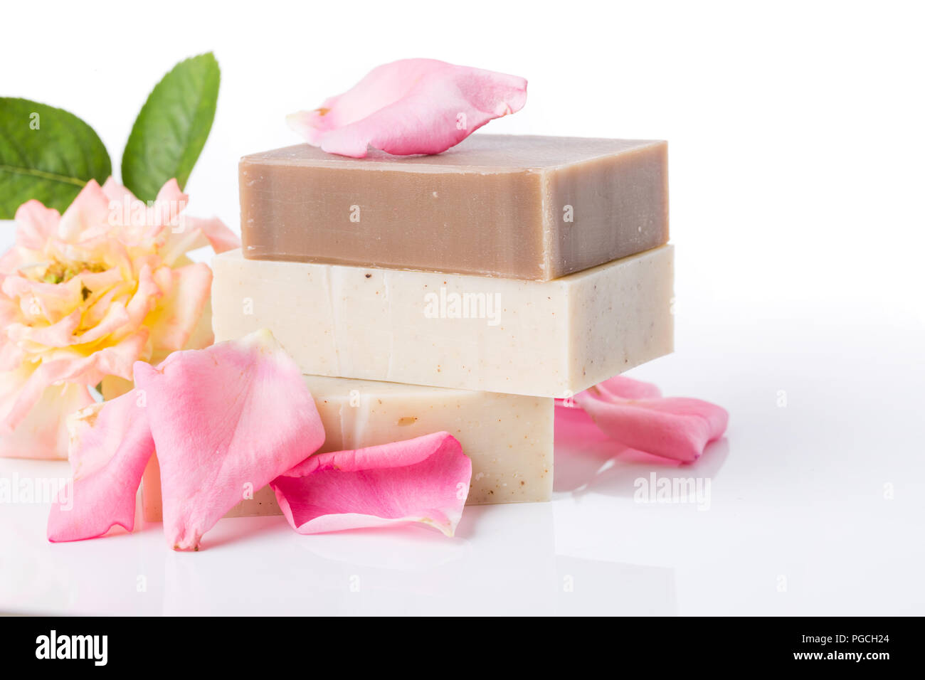 Top view of handmade soap with flower petals on white background - Stock Image