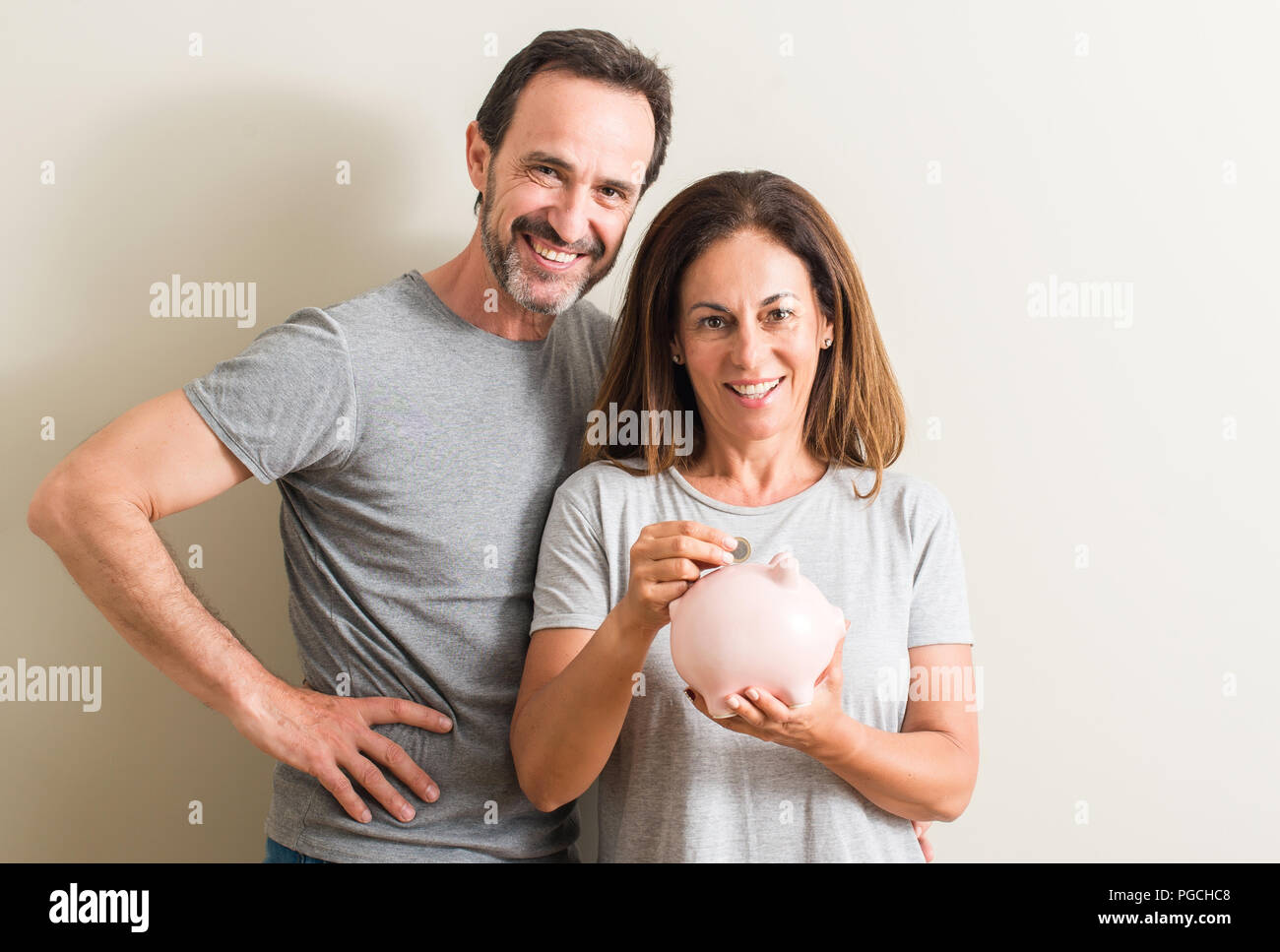 Middle age couple, woman and man, holding piggy bank with a happy face standing and smiling with a confident smile showing teeth - Stock Image