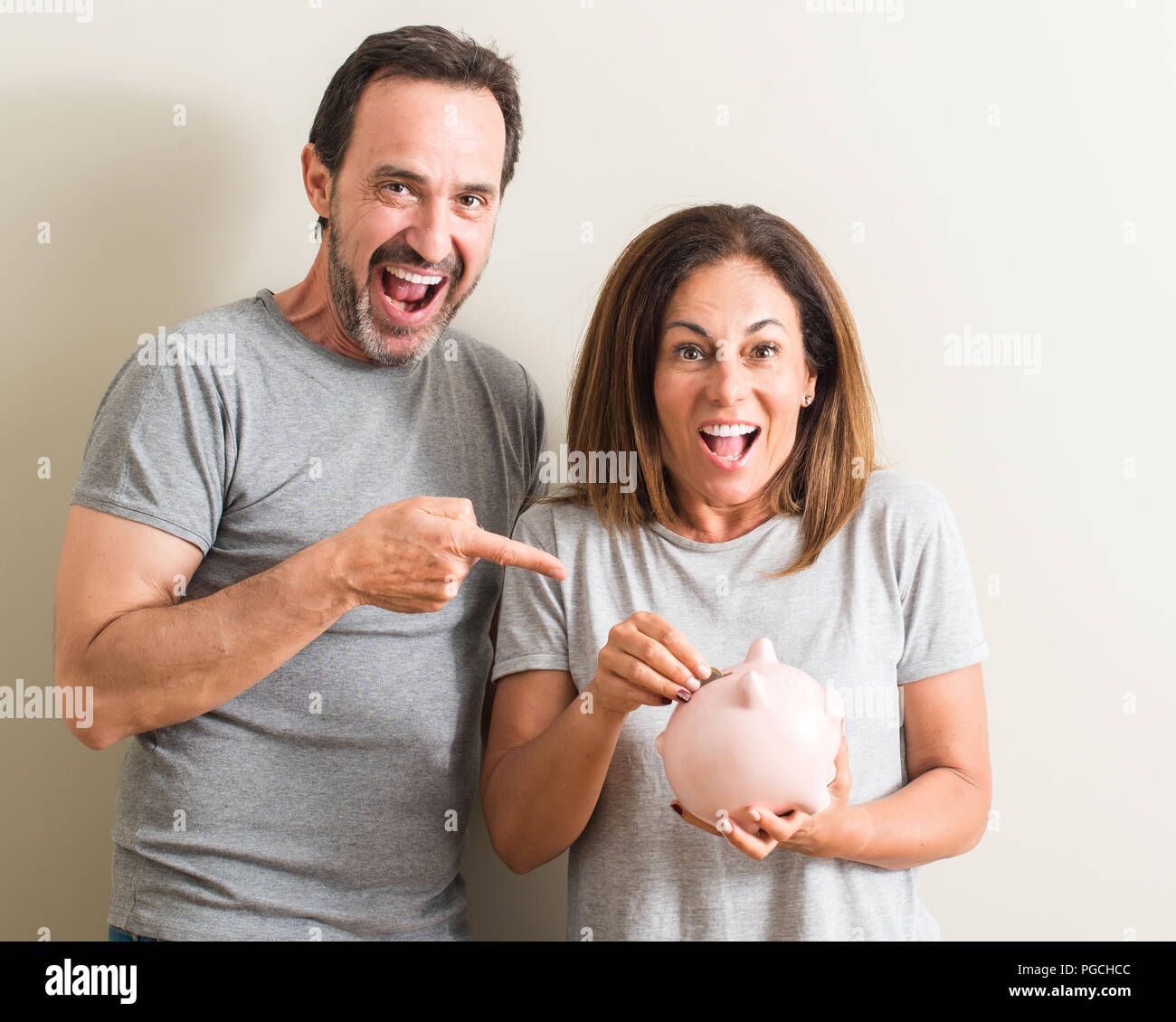 Middle age couple, woman and man, holding piggy bank very happy pointing with hand and finger - Stock Image