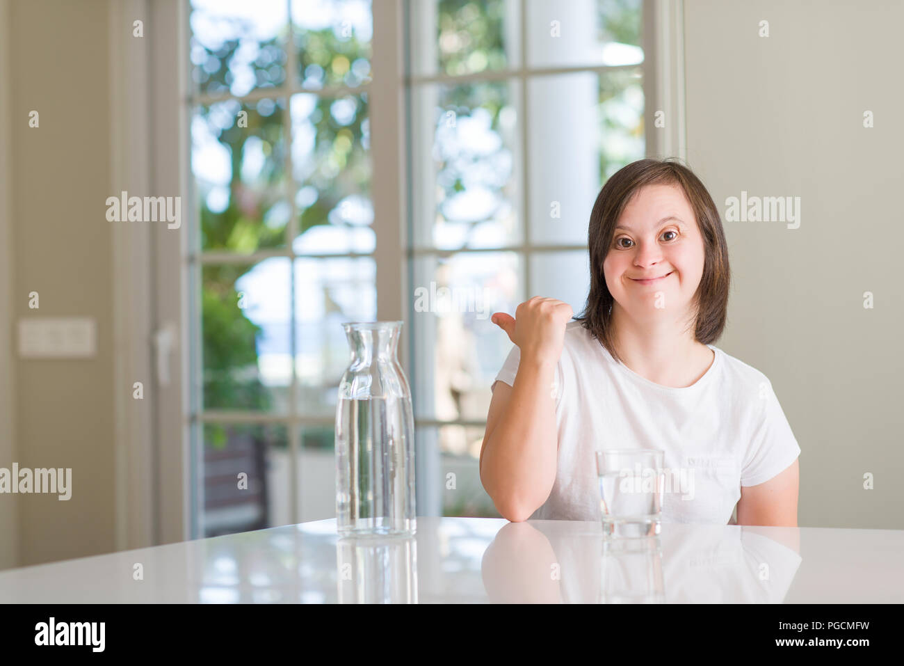 down syndrome woman at home drinking water pointing and showing with rh alamy com woman at home bio-oil woman at home bio-oil