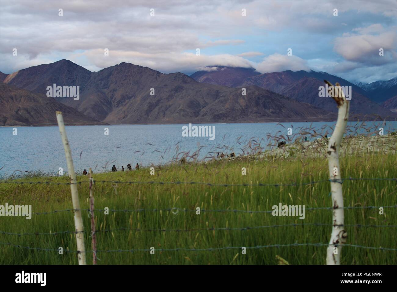 'Pengong Lake'. Fencing is always representative of Human limitations. We cant limit the Mother Nature. - Stock Image