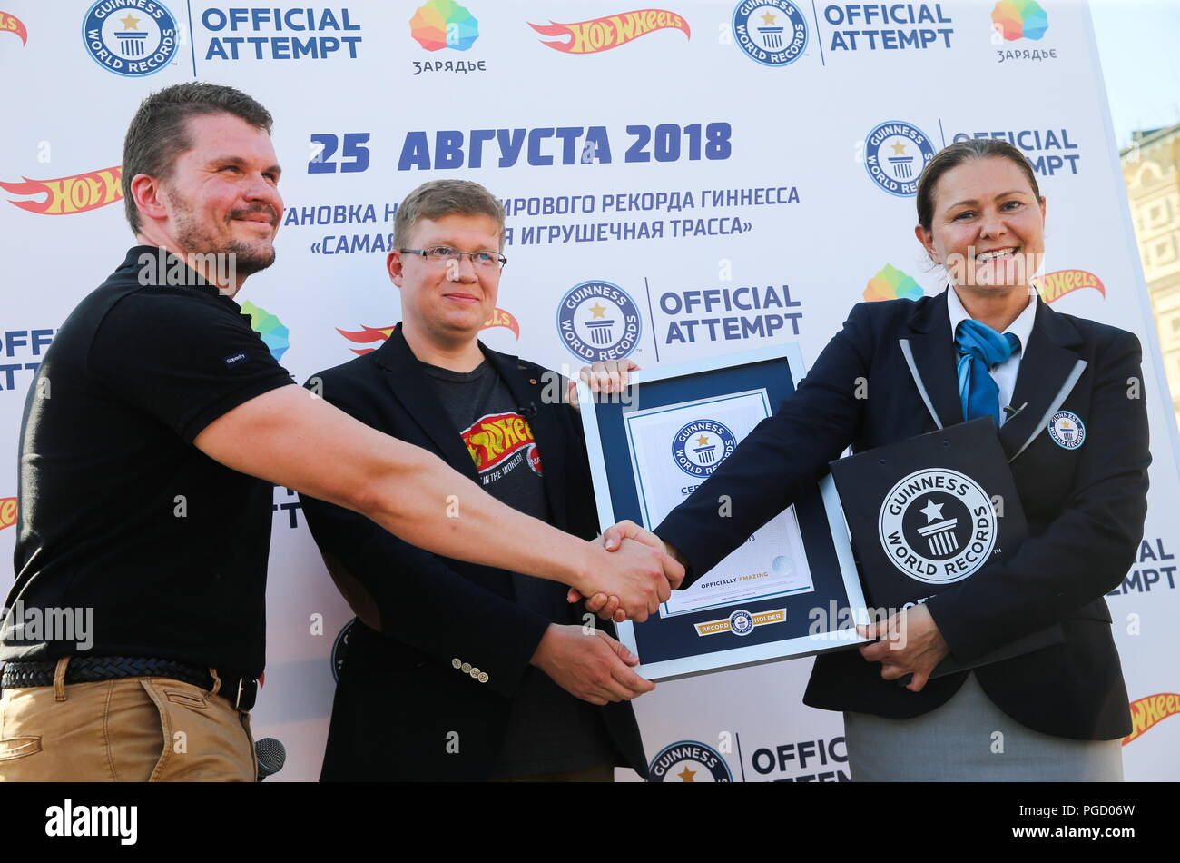 Moscow, Russia. 25th Aug, 2018. MOSCOW, RUSSIA - AUGUST 25, 2018: Guinness World Records representative Sheyda Subashi-Gemidji (R) gives a certificate to Hot Wheels Russia officials Kirill Frolov and Alexei Dmitriyev (L-R) as Hot Wheels brand toy cars have successfully completed the track loop of 560m [1,837ft] in length at Moscow's Zaryadye Park, thus beating the previous Guinness world record of 554m set in the US for the largest Hot Wheels track loop. Vladimir Gerdo/TASS Credit: ITAR-TASS News Agency/Alamy Live News - Stock Image