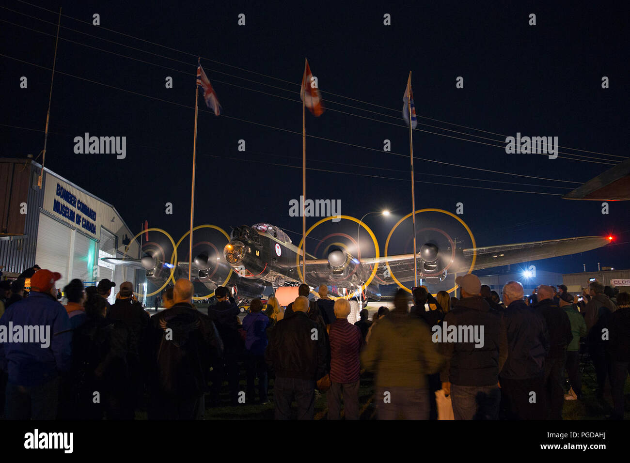 Nanton, Canada. 24th August, 2018. Visitors at the Bomber Command Museum of Canada watch as a Lancaster Bomber is started up during a night engine run. The event is part of a 75th anniversary commemoration of the Dambusters Raid during World War II. Rosanne Tackaberry/Alamy Live News Stock Photo
