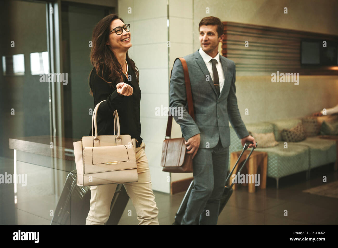 Two business travelers walking through airport lobby with their luggage and having a friendly chat. Businessman and businesswoman going on a business  - Stock Image