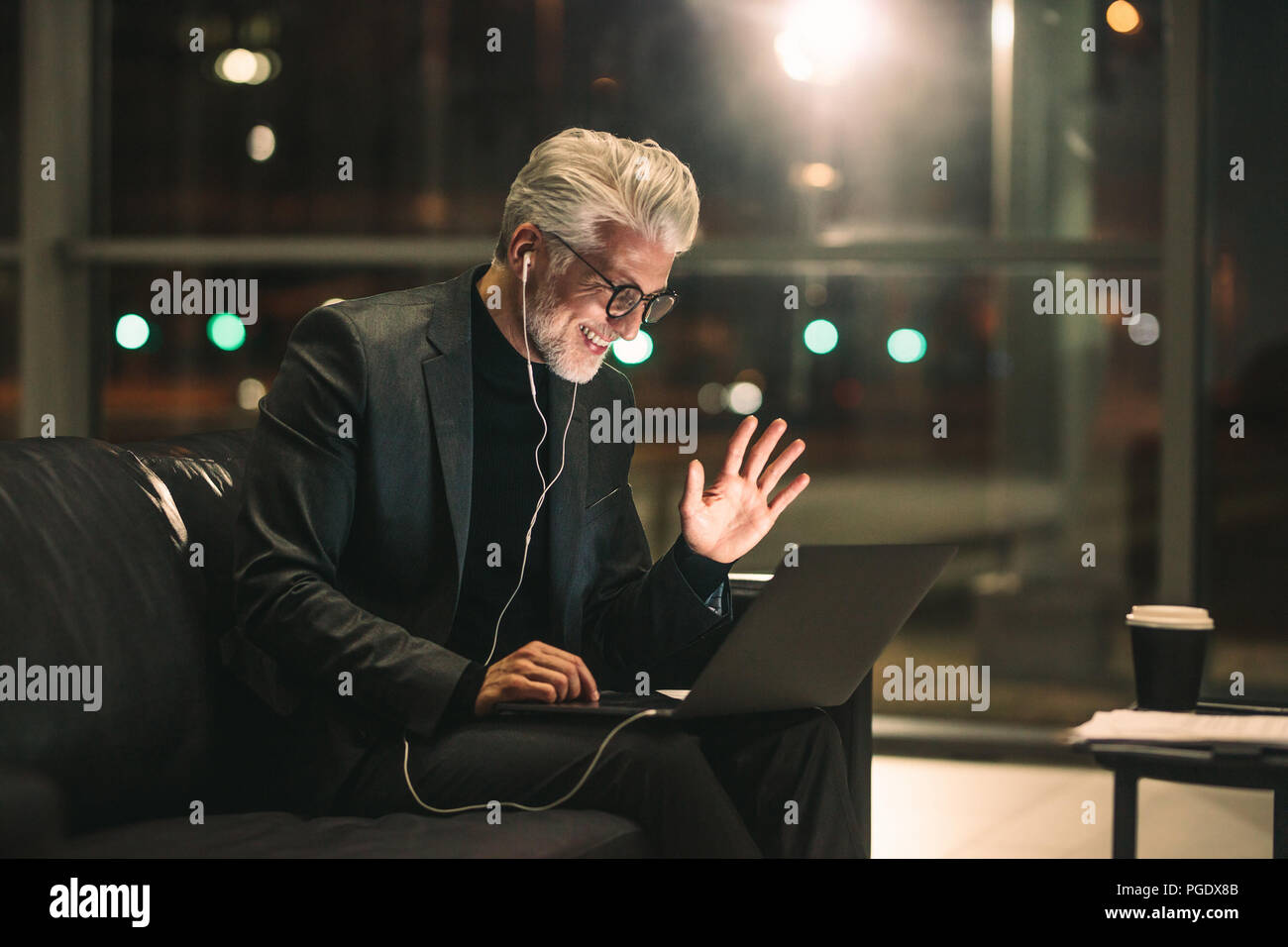 Middle aged man on video call using a laptop in office lobby. Smiling businessman late at night in office making gestures on a video call. - Stock Image