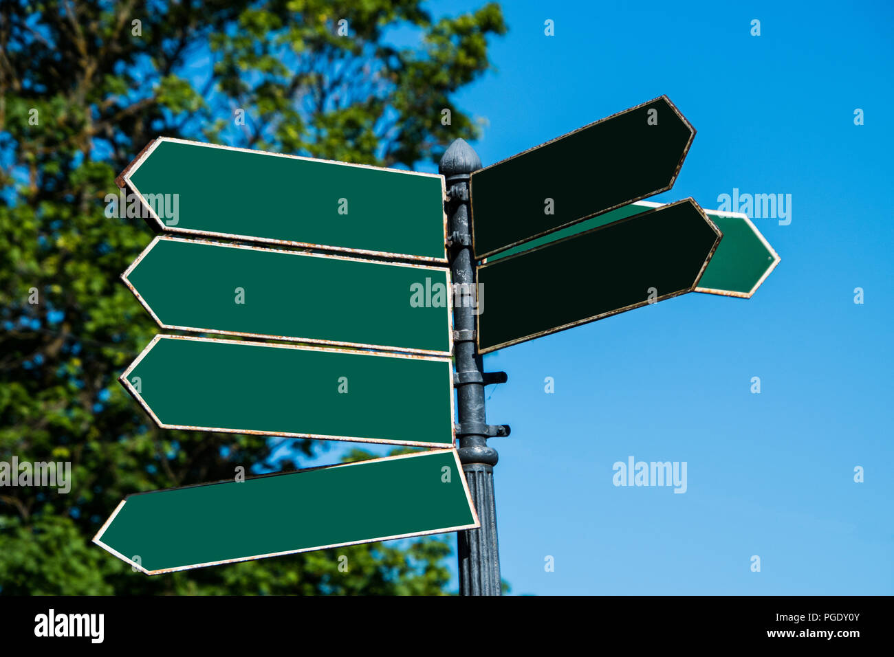 Multiple blank green arrow shaped directional street signs on a pole pointing in various directions - Stock Image