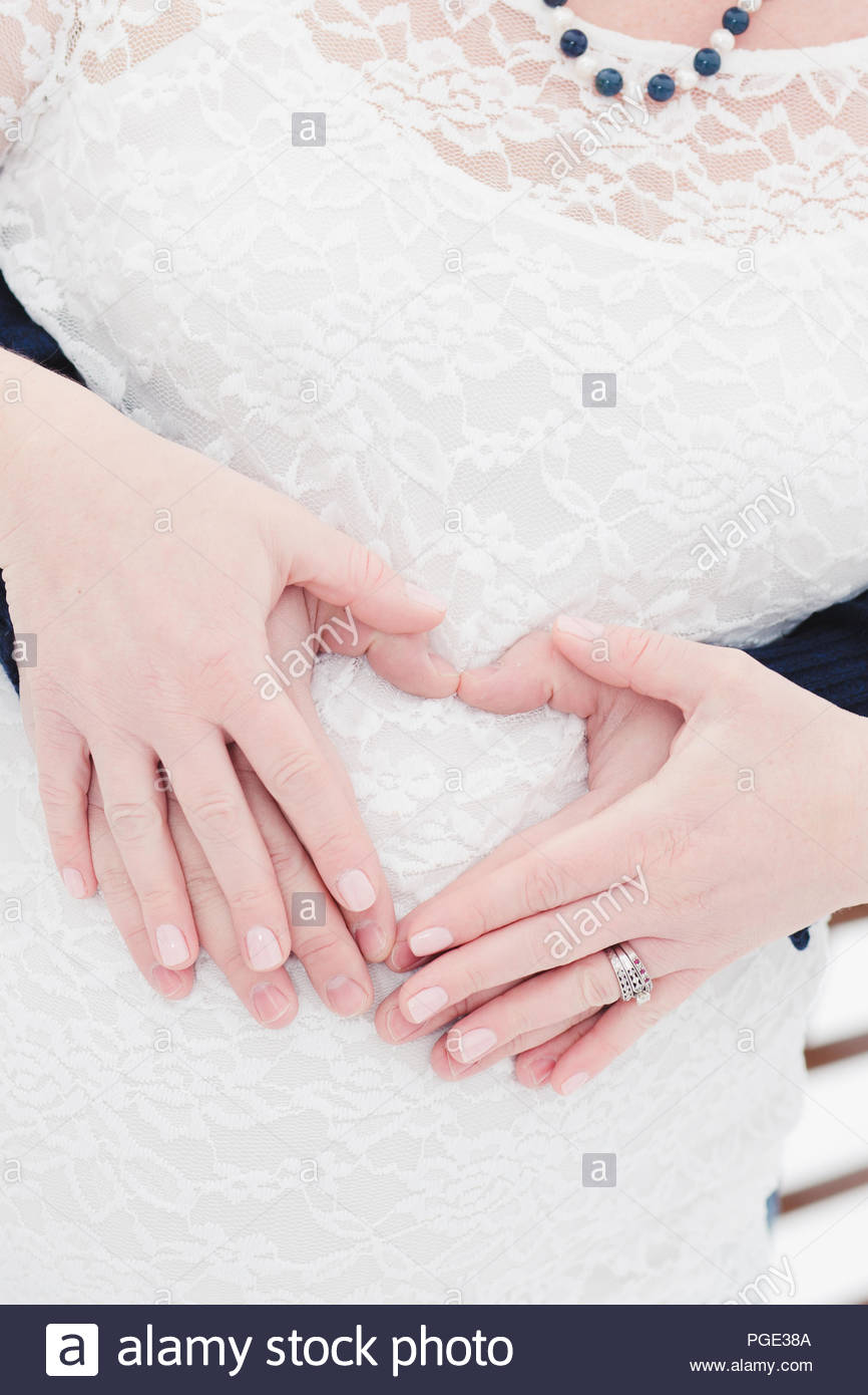 Couple with heart shaped hands over pregnant belly Stock Photo ...
