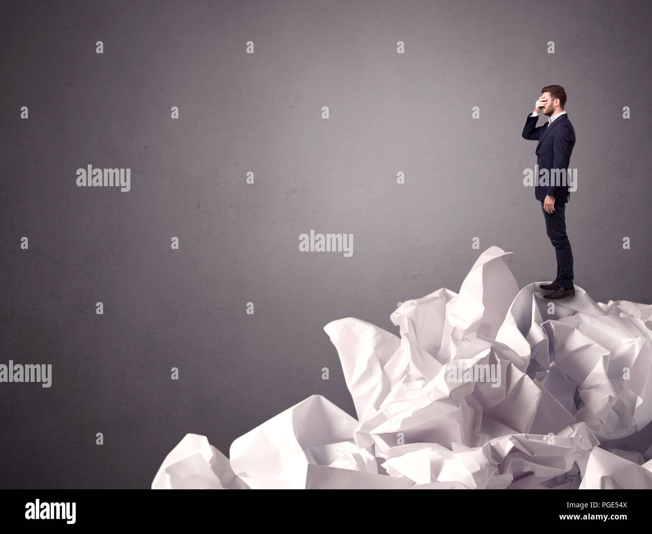 Thoughtful young businessman standing on a pile of crumpled paper with a grungy grey background - Stock Image