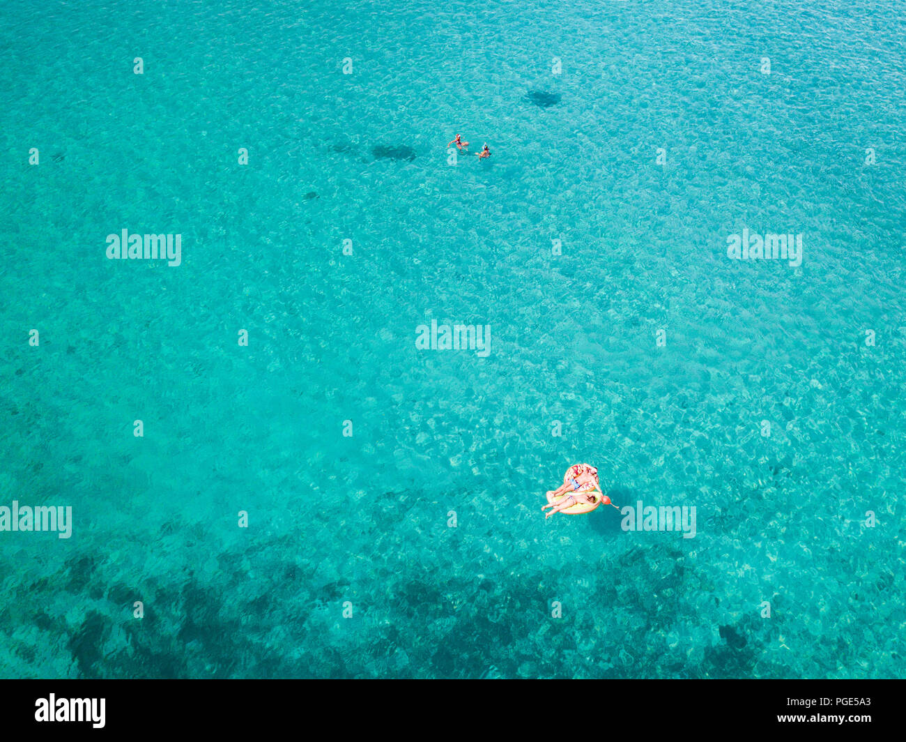 Aerial view of two people relaxed on an inflatable mat floating on a beautiful turquoise sea. Cala Brandinchi, Sardinia, Italy. Stock Photo