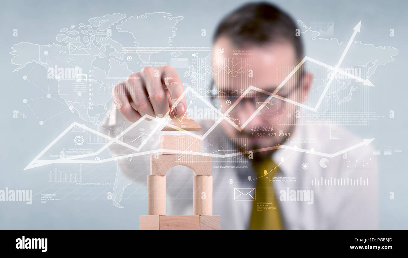 Young handsome businessman using wooden building blocks with data and calculations behind him Stock Photo