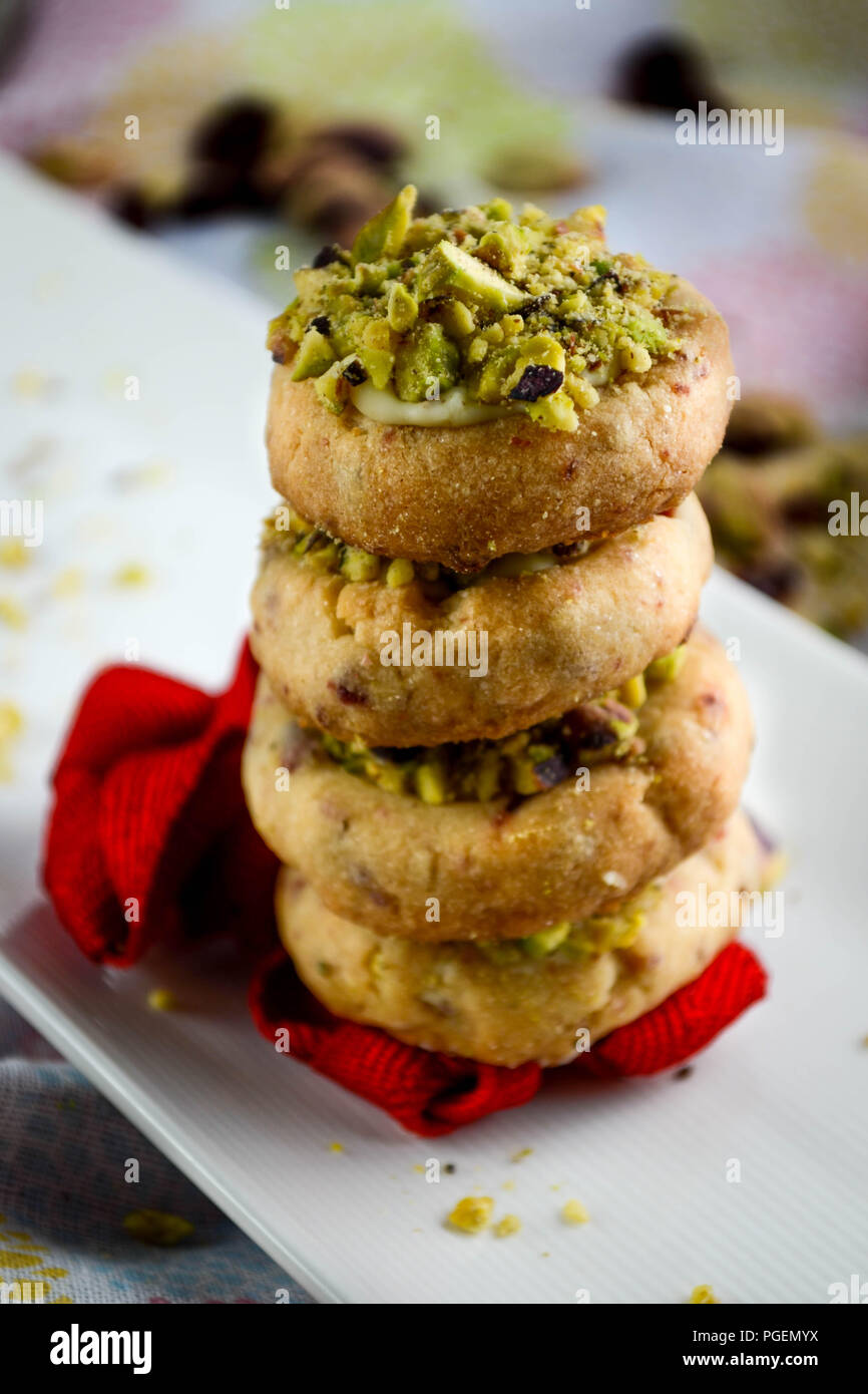 Miniature cranberry shortbread cookies with white chocolate and pistachios served on a plate and decorated with a red ribbon Stock Photo