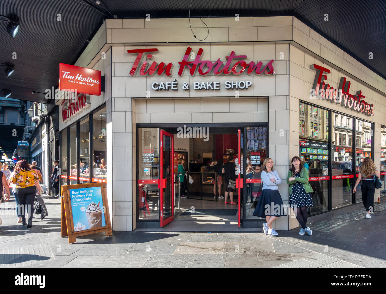Tim Hortons cafe and bake shop in central Glasgow with customers inside the shop and pedestrians / shoppers on the pavement outside. Scotland, UK. - Stock Image