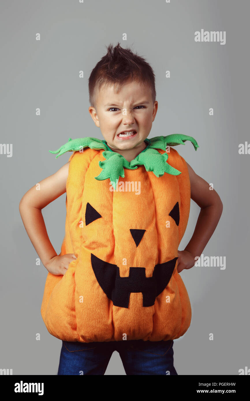 Portrait of adorable funny white Caucasian boy dressed as pumpkin for Halloween. Child playing having fun making faces in studio for autumn fall seaso Stock Photo