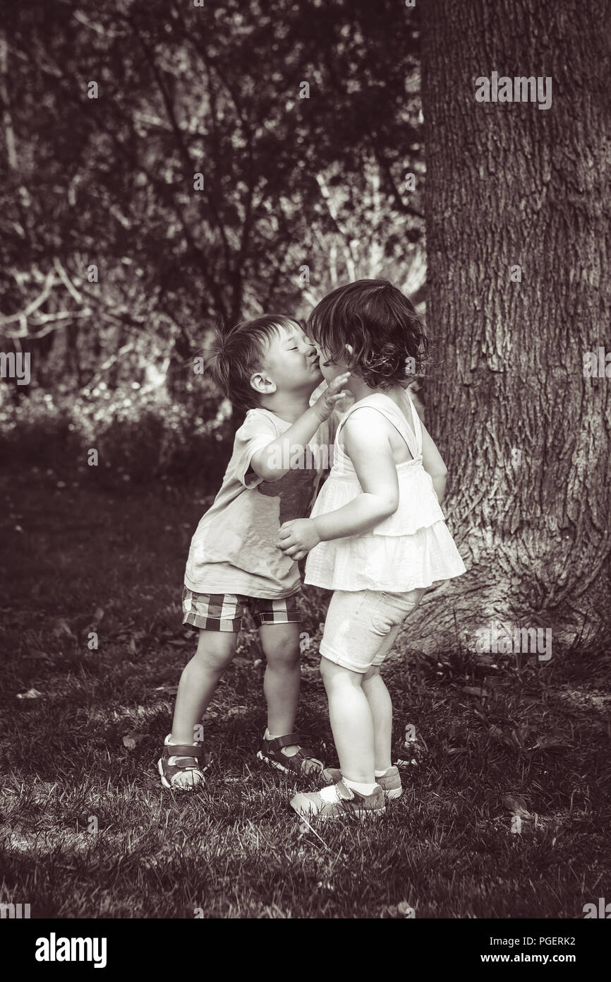 Black and white portrait of two cute adorable baby children toddlers hugging and kissing each other