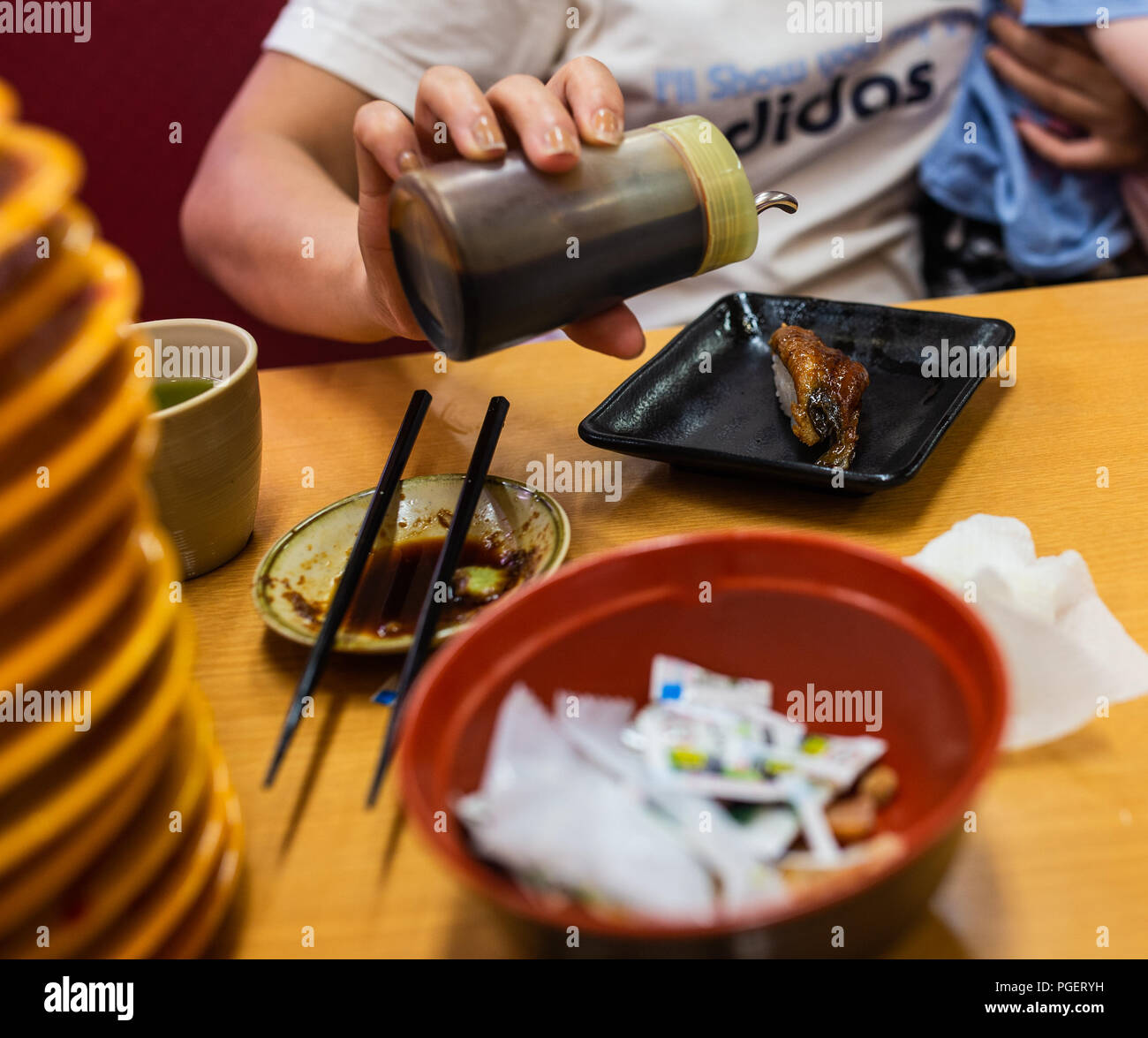 Woman putting soy sauce of sushi. - Stock Image