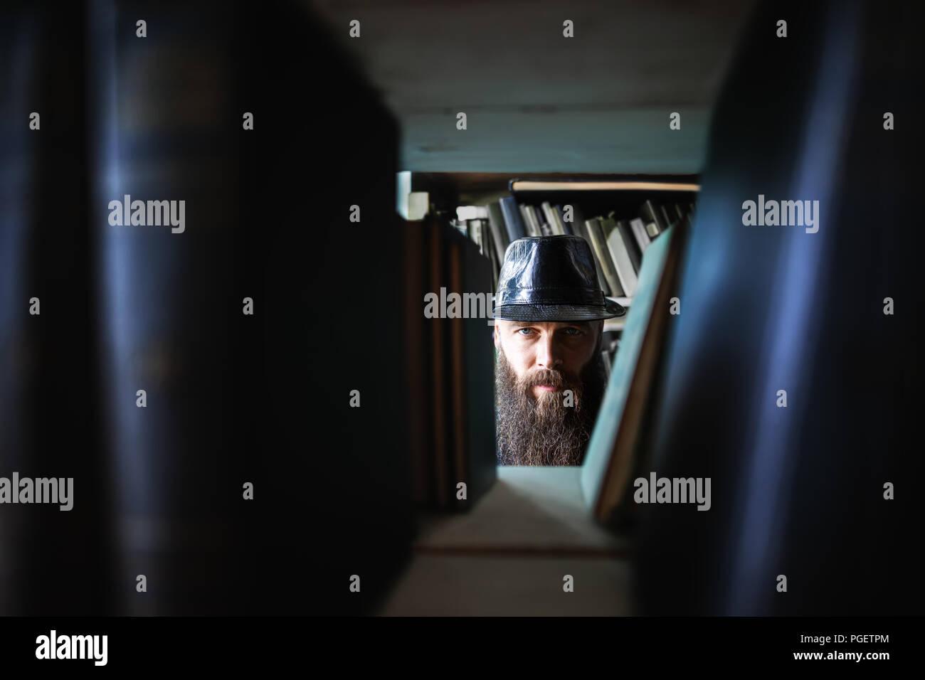 Bearded man spying through bookshelves. mystery сoncept Stock Photo
