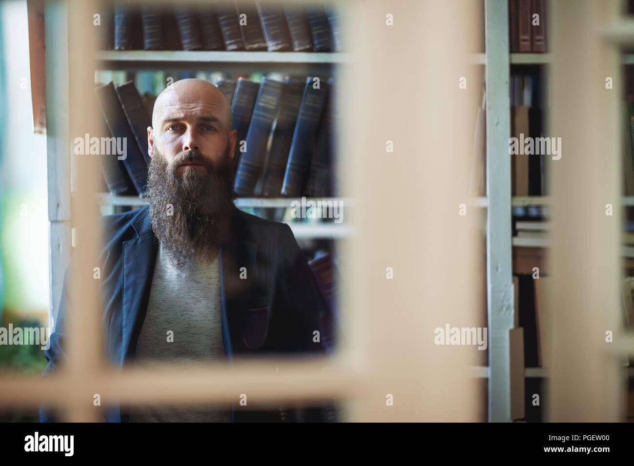 Bearded stylish man through window of library. Serious reader looks forward against background of bookshelves - Stock Image