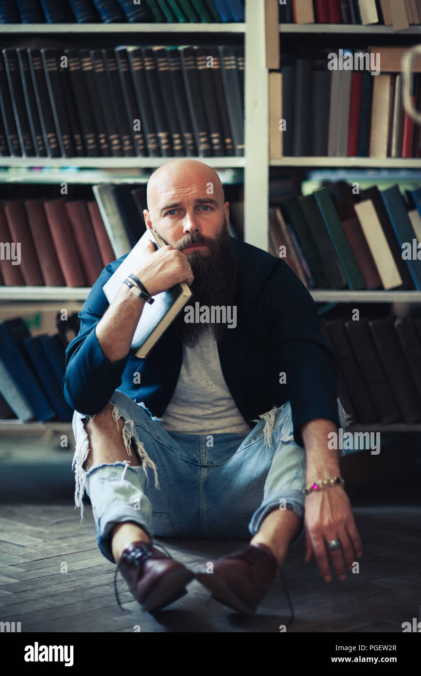 Bored stylish hipster man sitting on floor in library. Depression concept - Stock Image