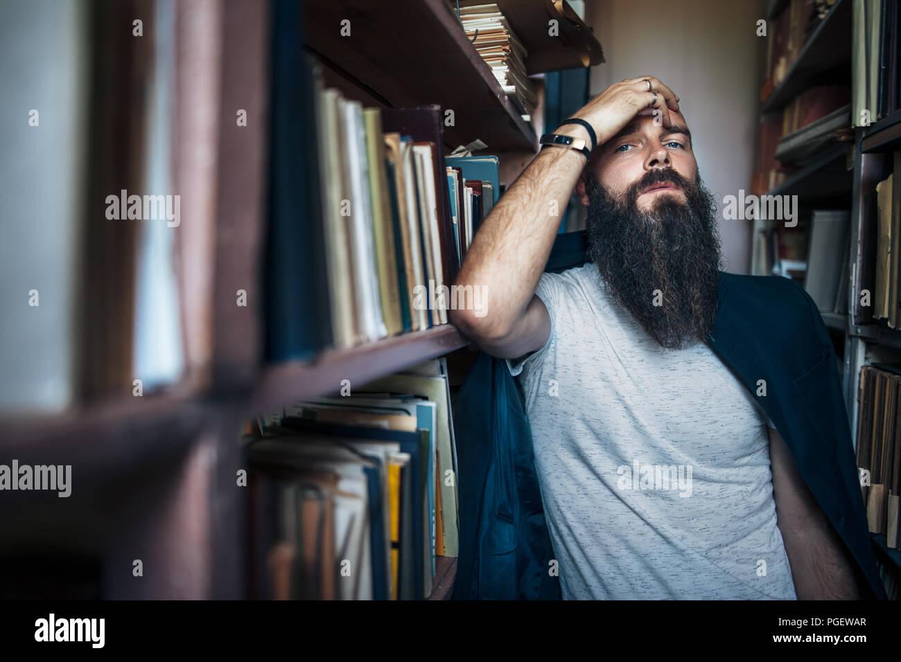 Thoughtful hipster man among bookshelves. Depression concept - Stock Image
