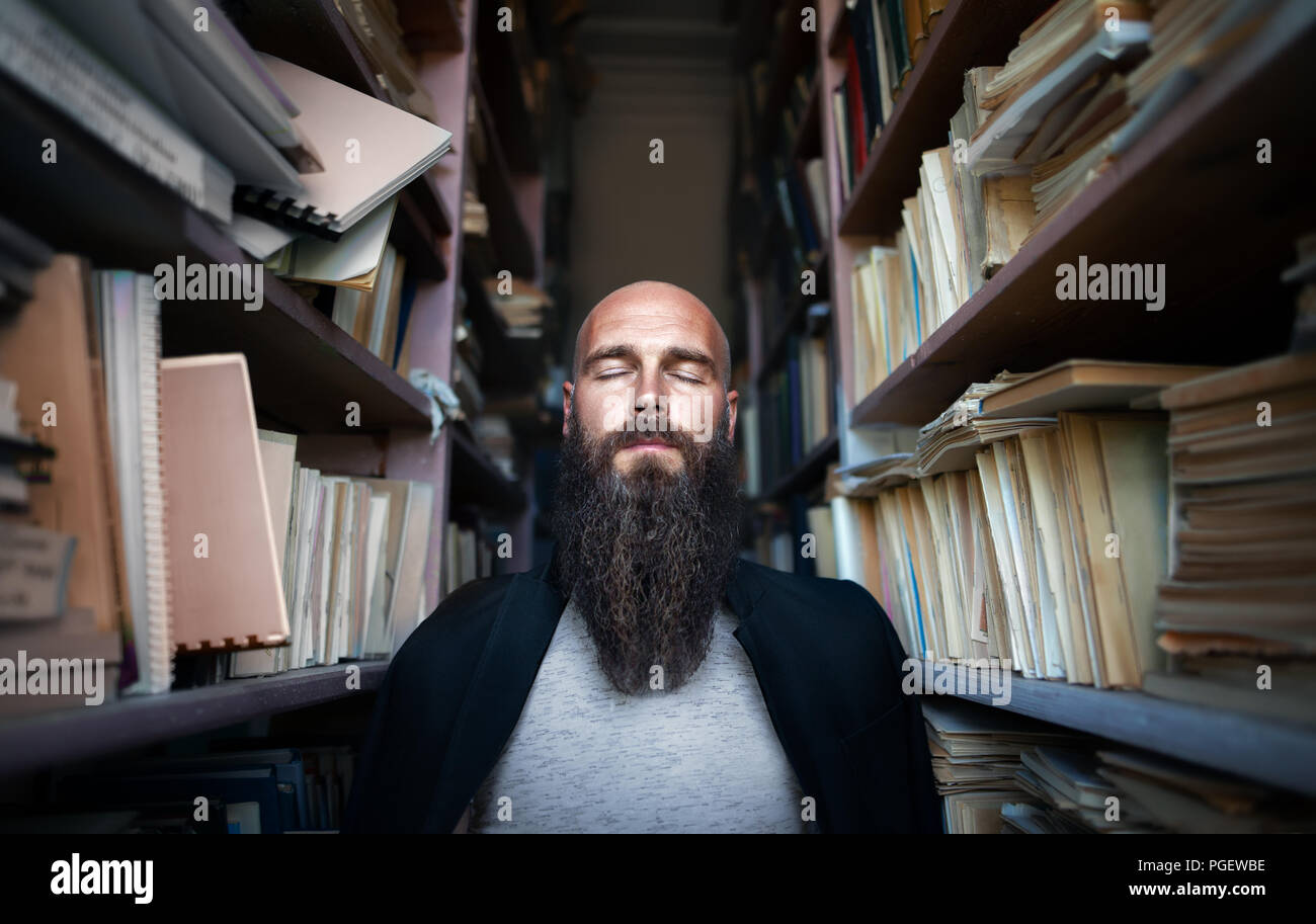 Portrait of bearded stylish hipster man with closed eyes in library. meditation - Stock Image