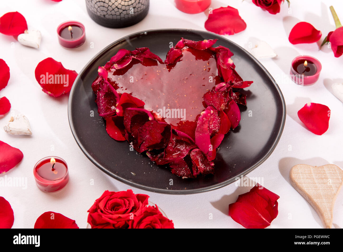 Romantic heart-shaped red cake with rose petals served on a white table decorated with candles,, rose petals and hearts for an anniversary or Valentin - Stock Image