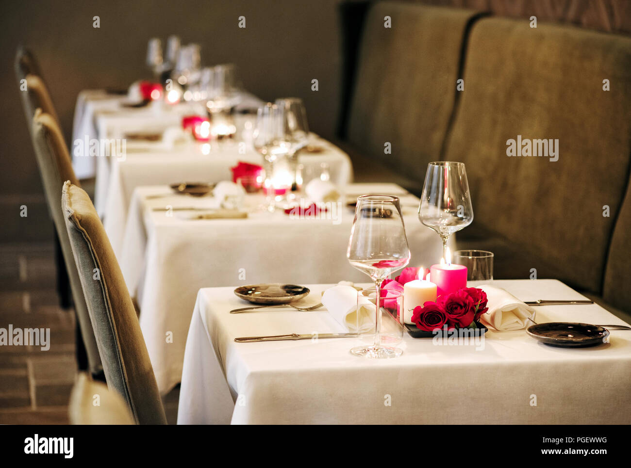 Romantic Table Settings In A Restaurant With Centrepieces Of Burning Candles And Red Roses And Elegant Glassware For An Intimate Dinner For Two Stock Photo Alamy